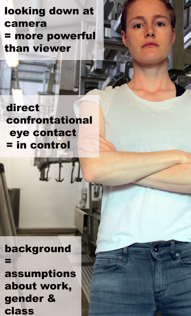 Picture shows model looking into the camera with arms folded.  Text reads: looking down at camera = more powerful than viewer.  Direct confrontational eye contact = in control.  Background = assumptions about work, gender and class.