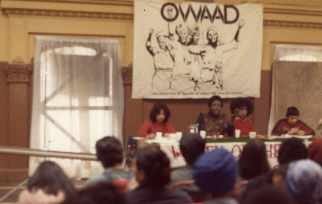 Image shows a panel of four OWAAD leaders on stage at the first OWAAD conference in 1979.