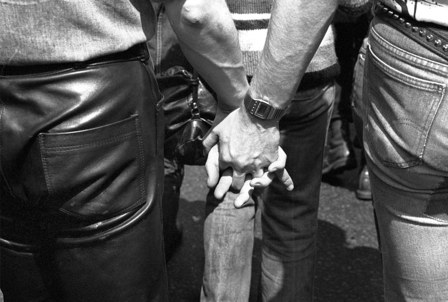 Two people holding hands at a Pride parade